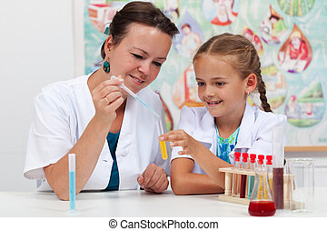 Teacher helping little girl student in science class