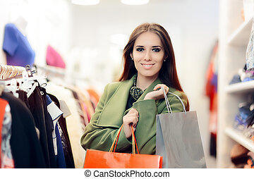 Elegant Shopping Woman Wearing a Green Coat in Fashion Store...