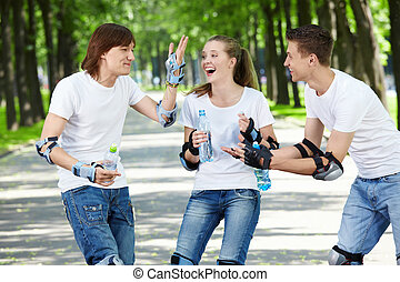 Young laughing people on rollers in park