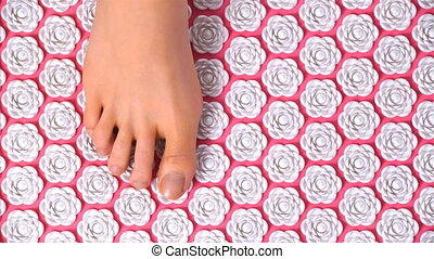 Female feet gently tread on acupuncture massage mat. Top...