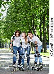 Rollers - Three young people on rollers in park