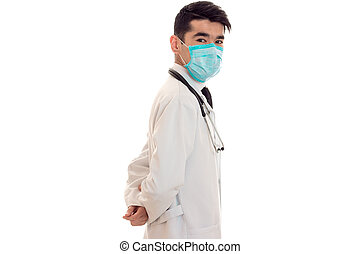 doctor in a white lab coat stands sideways with a mask on...