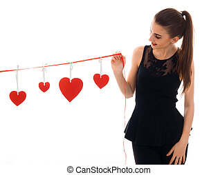 a young girl in a black dress holding a Ribbon with hearts...