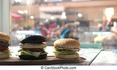 Three burgers on wooden board. Hamburgers on cafe table. Buy...