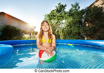 Happy girl playing with ball in swimming pool - Happy...