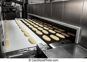 Production of bread at the bakery - Raw dough bread on a...