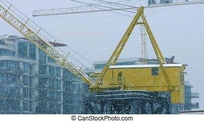 Crane Near Buildings In Heavy Snowfall - Large yellow crane...