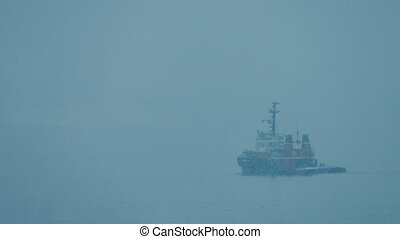Boat Passing In Winter Snowstorm - Small boat sailing past...