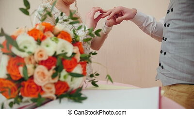Beauty bride and handsome groom are wearing golden rings...