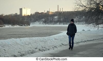A beautiful girl walks in Park at winter