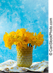 Bright yellow Narcissus flowers bouquet in a yellow glass...