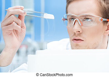 scientist in protective glasses and gloves looking at...