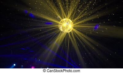 Disco ball spinning in a club - Yellow disco ball shining...