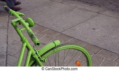 Green Bike Front Wheel People Walking - A green colored bike...