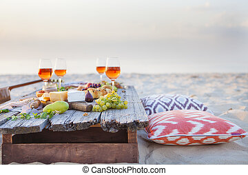 Picnic on the beach at sunset in boho style, food and drink...