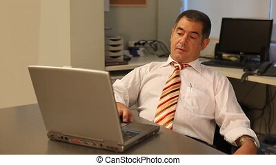 Tired businessman using laptop