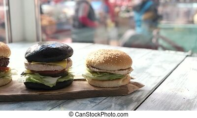 Three hamburgers on wooden board. Burgers in cafe.