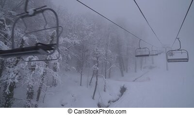 Chairlift for 4 persons in clouds at ski resort Gorky Gorod