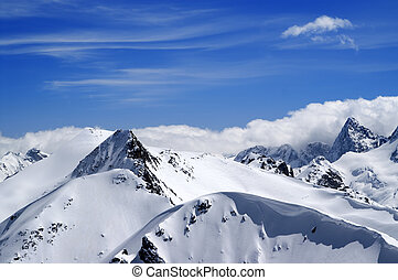 Winter mountains with snow cornice and blue sky with clouds...