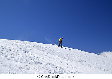 Snowboarder downhill on off-piste slope and blue clear sky....