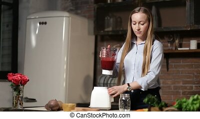 Woman pouring beet smoothie from blender into jar -...