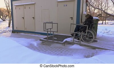 Disabled man on wheelchair drive near to public toilet