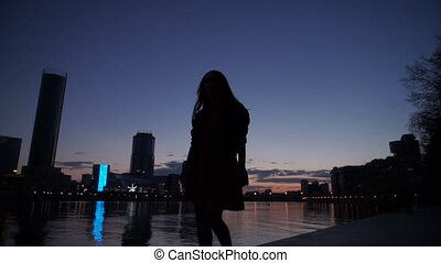 Silhouette of the girl at night on the river bank in the...