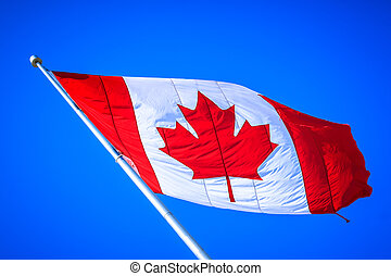 Canadian flag with blue sky as background