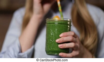 Woman drinking green detox vegetable smoothie - Closeup...