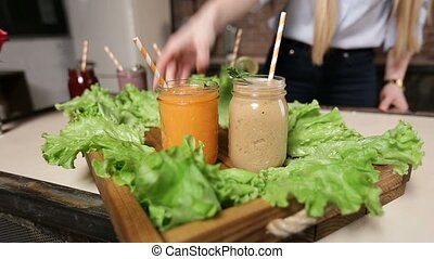 Woman serving tray with colorful smoothies - Closeup female...