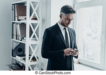 Quick message. Good looking young man in full suit using his...