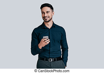 Receiving good news. Handsome young man holding smart phone and smiling while standing against grey background