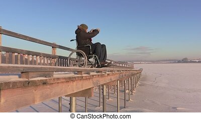 Disabled man on wheelchair using tablet on the bridge near...