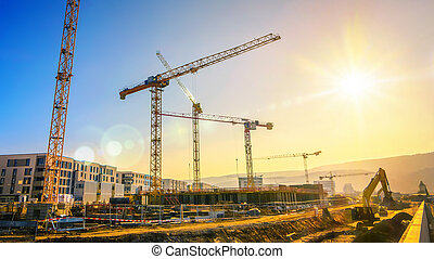 Large construction site including several cranes, with clear...