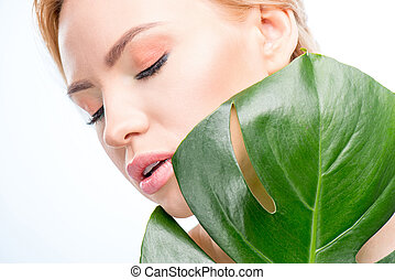 sensual woman with closed eyes holding green leaf, skincare concept