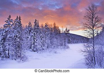 Sunrise over a river in winter near Levi, Finnish Lapland -...