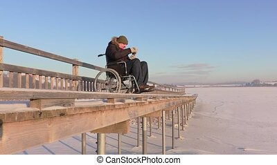 Disabled man on wheelchair near lake in winter