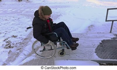 Disabled man on wheelchair trying to drive to entrance door