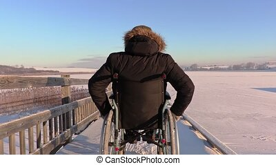 Happy disabled man on wheelchair near lake in winter