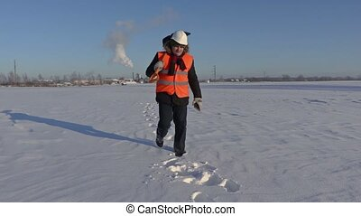 Worker with snow shovel walking and using tablet in factory