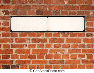 Old blank white British street sign on a red brick wall.