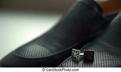 Man shoes and cufflinks pan shot