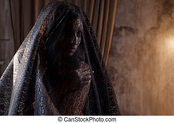 Mysterious portrait of beautiful woman in black lace veil