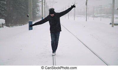 Portrait of a young handsome man with a beard. A bearded man walking on railroad tracks winter. Healthy young bearded man in nature.