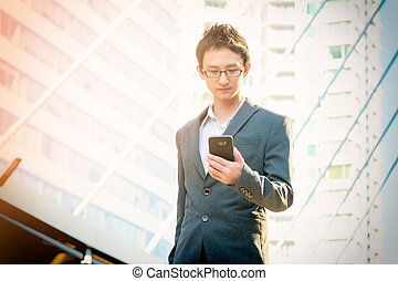 Casual businessman using smartphone in the city background