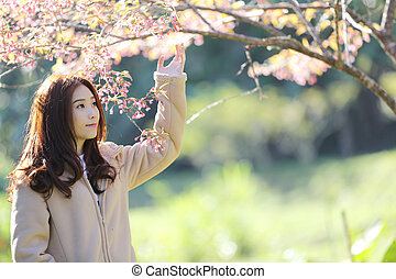 beautiful young woman with blooming cherry blossoms sakura flowers