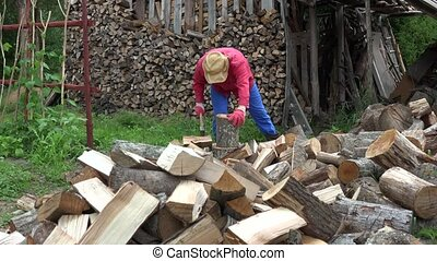 Villager guy prepare organic wood fuel near woodshed for...