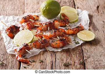 Tiger prawns wrapped in bacon on skewers with thyme and lime...