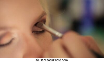 Makeup artist doing makeup for young blonde caucasian woman