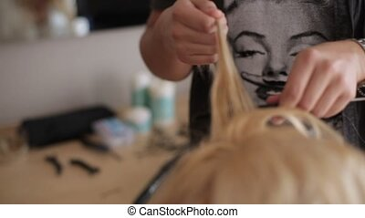Hairdresser at work with blonde woman model